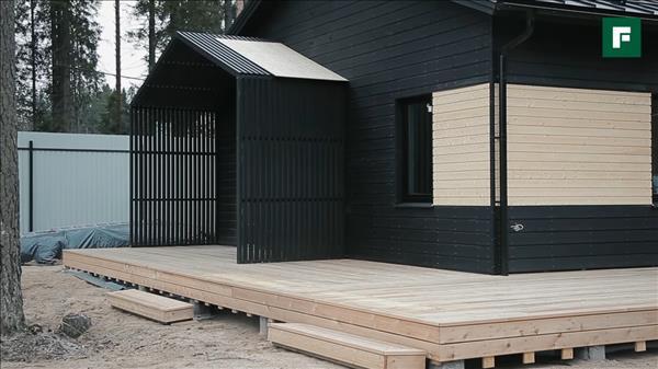 Дом черного цвета с террасой по скандинавской технологии